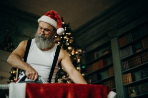 Santa ironing his suit, looks similar to the Santa from the Christmas Chronicles movie. Top 3 Christmas Movies